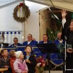 Pfarrer Helbig mit gestreckter Hand gen Himmel studiert mit den Kindern ein Lied ein